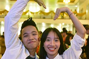 A boy and girl at blue dragon forming a heart shape